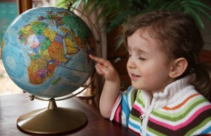 child closing eyes pointing to globe