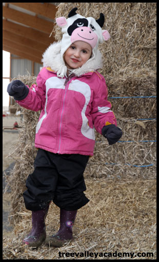 A girl playing on a haystack in a barn.