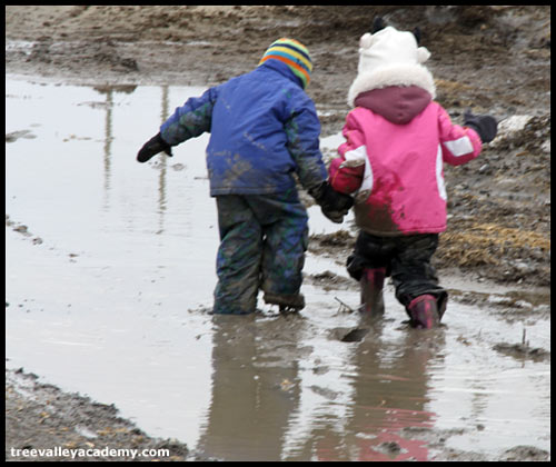 two children holding hands and walking through mud puddle