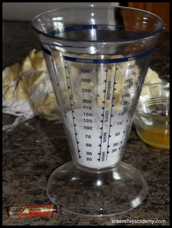 Using a german measuring cup to measure sugar.